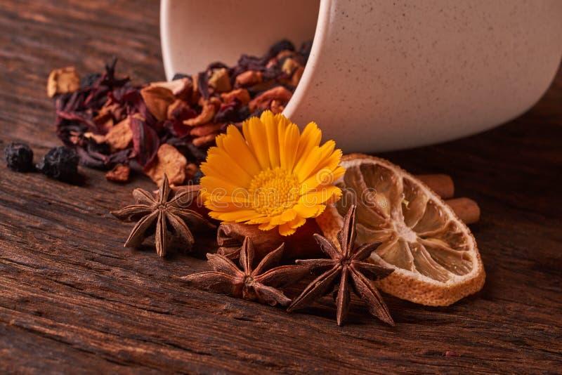 tazza e foglie crema di tè, dei frutti e del tè della frutta secca sul fondo di legno rustico della tavola Fuoco selettivo immagine stock libera da diritti