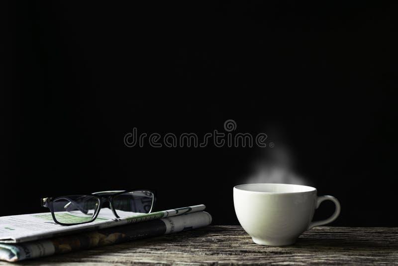 Tazza e giornale di caffè con vetro su di legno nel fondo scuro fotografia stock libera da diritti