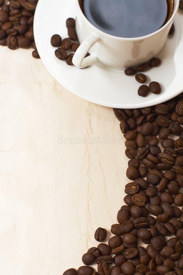 Tazza e granulo di caffè su vecchio documento immagine stock
