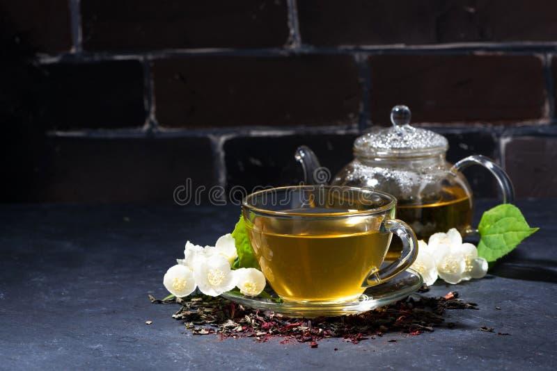 tazza e teiera del tè fragrante del gelsomino su un fondo scuro immagini stock