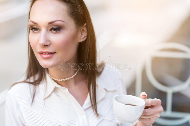 Tazza femminile pensierosa dell'assaggio della bevanda calda fotografie stock libere da diritti