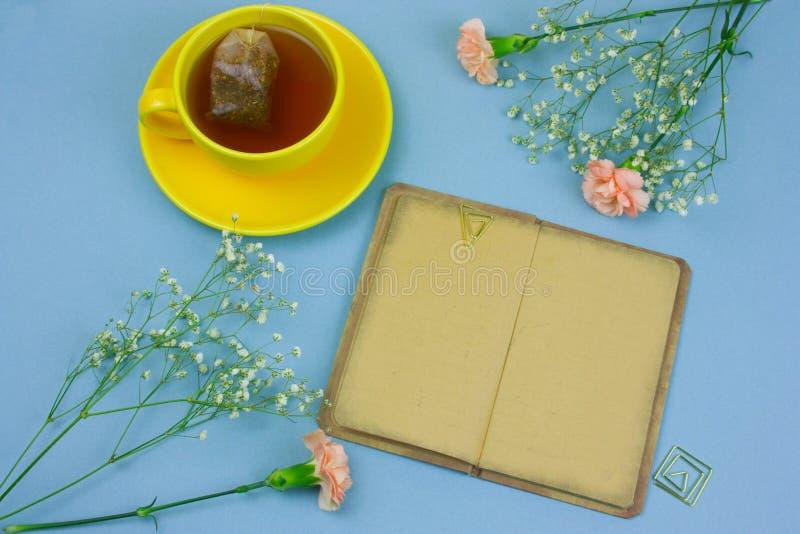 tazza gialla con tè e la bustina di tè, libro d'annata e fiori del garofano su una disposizione piana della molla blu del fondo immagine stock libera da diritti