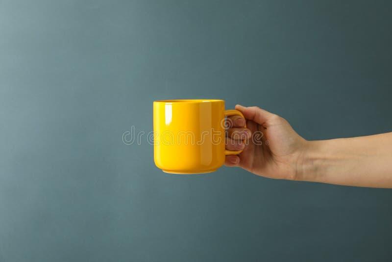 Tazza gialla della tenuta femminile della mano contro fondo nero fotografie stock libere da diritti