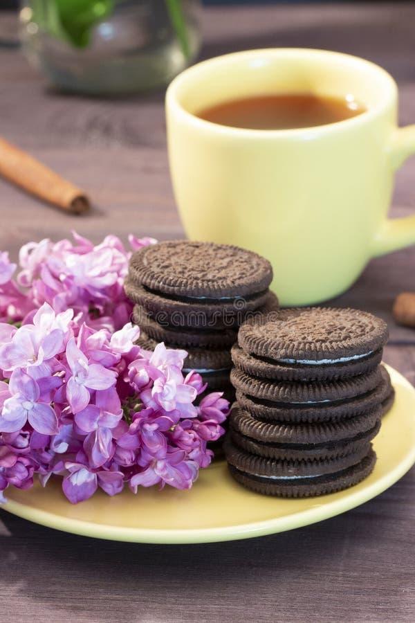 Tazza gialla di tè con i biscotti del cioccolato con un ramoscello del lillà e della cannella Servizio giallo di natura morta del fotografia stock libera da diritti