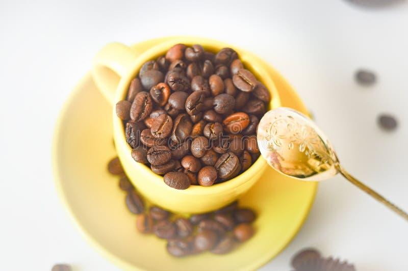 Tazza gialla in pieno dei chicchi di caffè naturali, vista superiore, su un fondo bianco Fuoco selettivo tazza di caff? che veste fotografia stock libera da diritti
