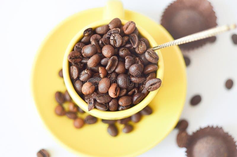 Tazza gialla in pieno dei chicchi di caffè naturali, vista superiore, su un fondo bianco Fuoco selettivo tazza di caff? che veste fotografie stock