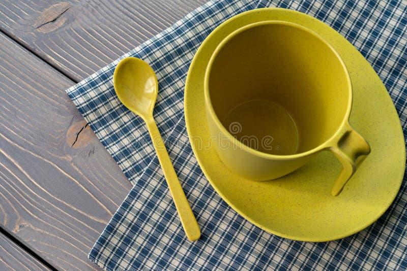 Tazza gialla su un piattino con un cucchiaio Utensili di bambù, con un tovagliolo a quadretti su una tavola di legno Profondit? b fotografia stock
