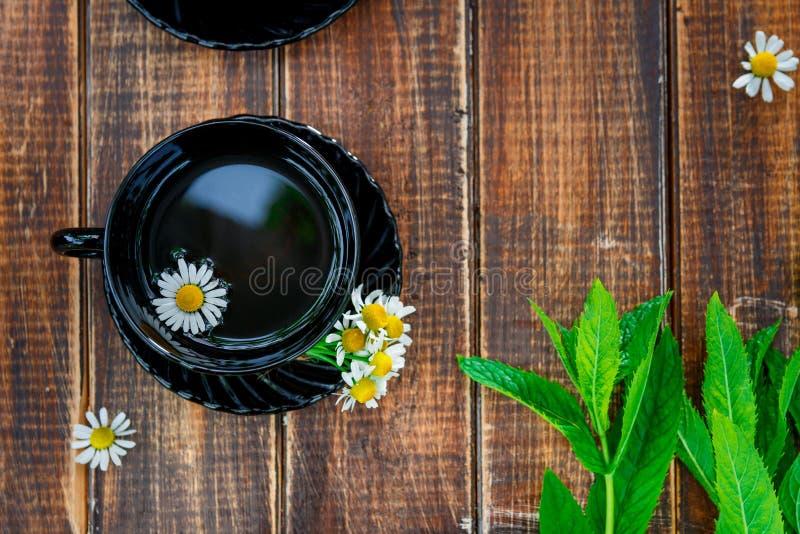 Tazza nera di tè con la camomilla vicino alla menta fresca sul fondo di legno della tavola Concetto Pagina, spazio della copia Vi immagine stock