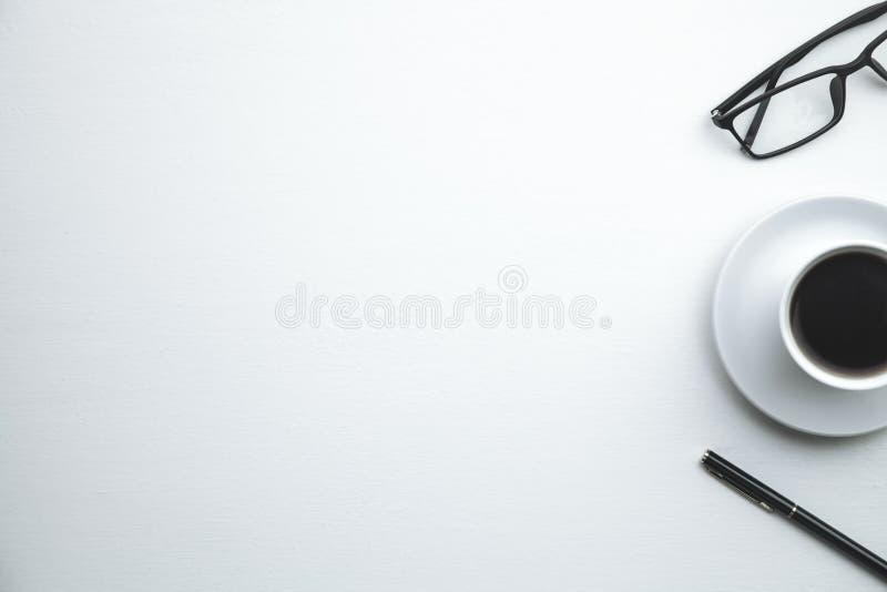 Tazza, penna e vetri di caffè su un fondo bianco fotografia stock libera da diritti