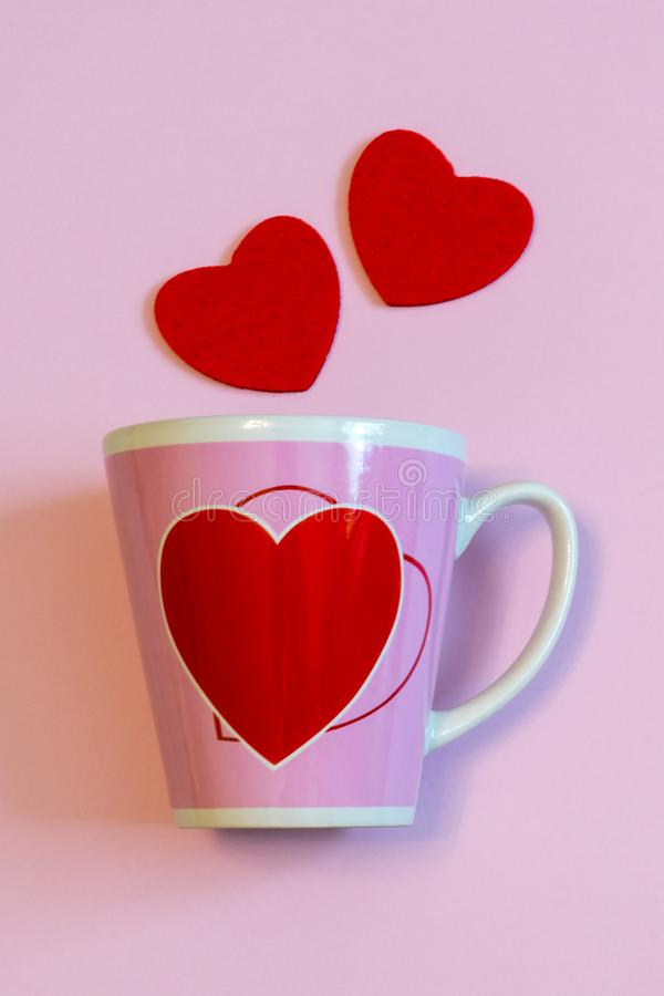 Tazza per caffè o tè e due cuori rossi su fondo pastello rosa Disposizione creativa nello stile minimo Amore, romanzesco, bigliet immagini stock