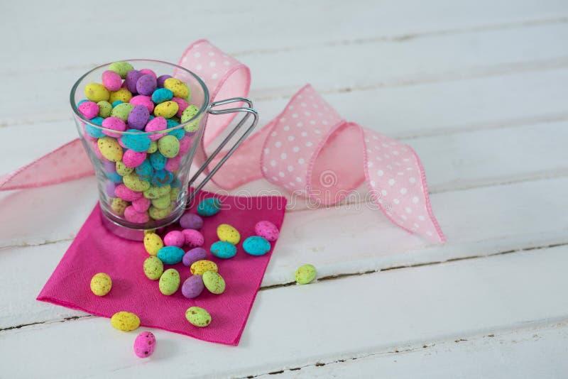 Tazza riempita di uova di Pasqua variopinte del cioccolato fotografia stock libera da diritti