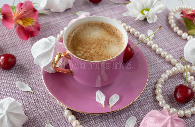 Tazza rosa con caffè ed i petali freschi fra le perle, i fiori ed i dolci immagine stock