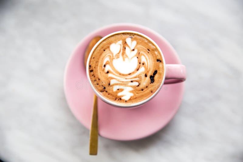 Tazza rosa di cappuccino con arte del latte del cigno sul fondo di marmo della tavola fotografie stock libere da diritti