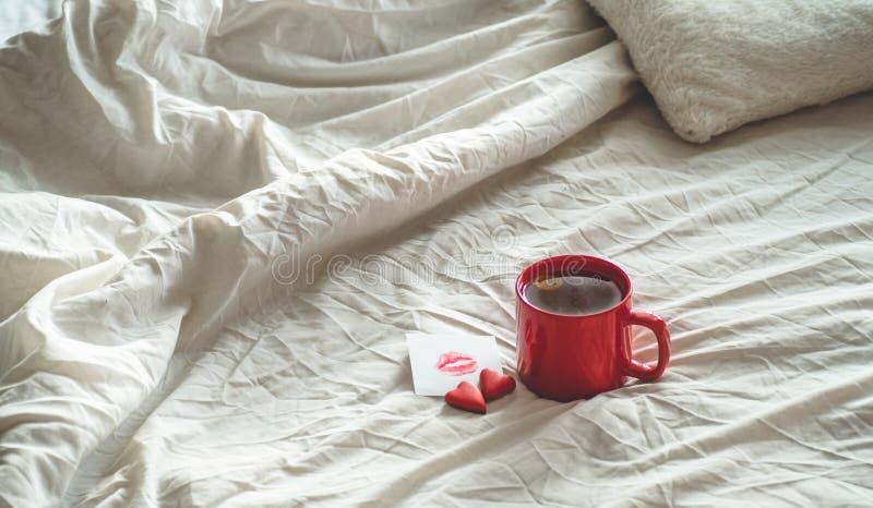 Tazza rossa di tè e di due biscotti dei cuori, una nota con un bacio su un letto bianco Concetto di giorno dei biglietti di S fotografia stock