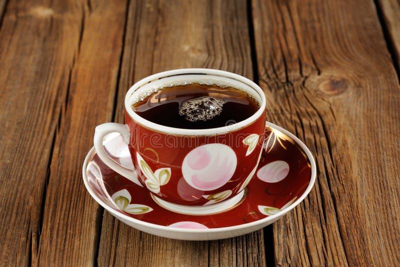 Tazza rossa di tè nero con le bolle su fondo di legno fotografia stock