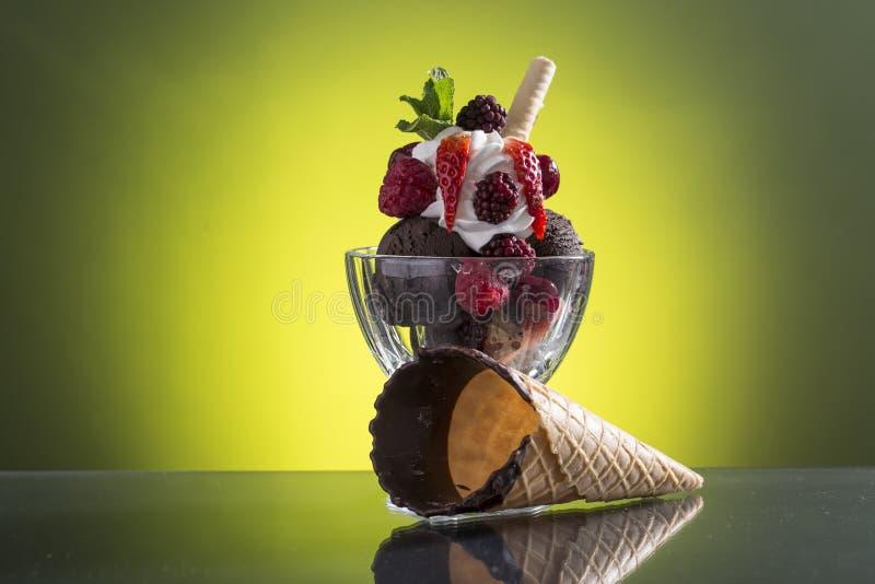 Tazza rossa variopinta del berrie con il ghiaccio del cioccolato e la panna montata immagini stock libere da diritti