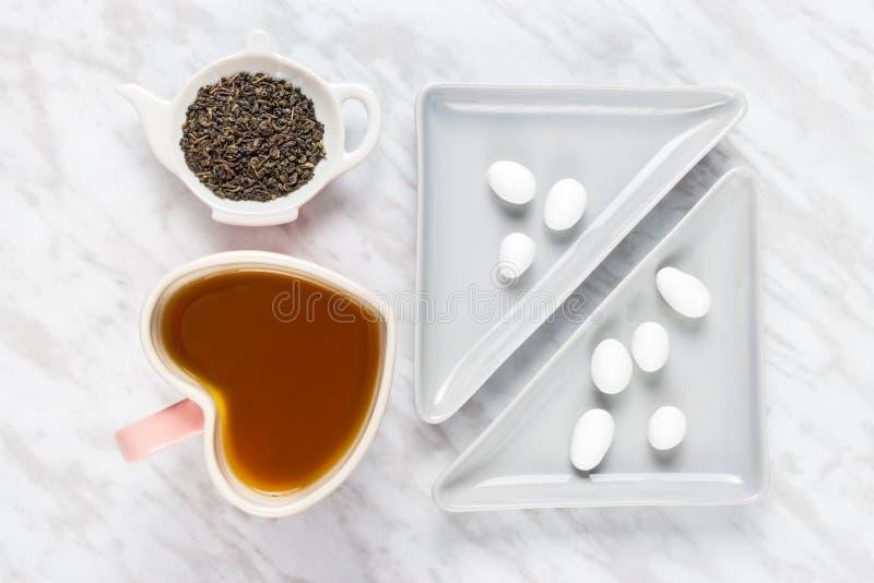 Tazza, tè verde e cioccolata bianca a forma di del cuore fotografia stock