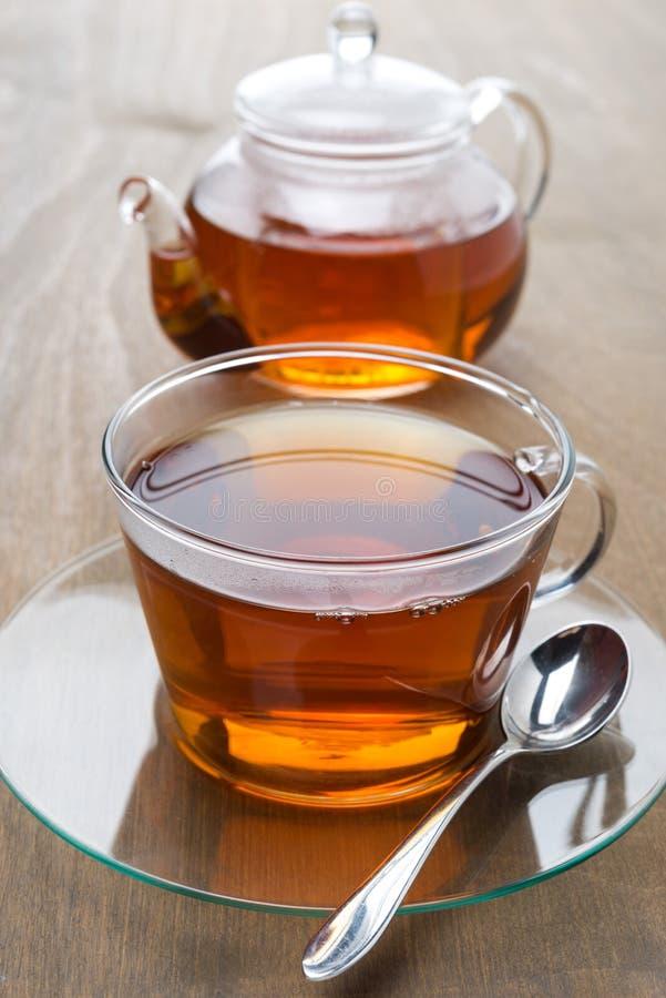 Tazza trasparente di tè nero e teiera su un fondo di legno immagini stock
