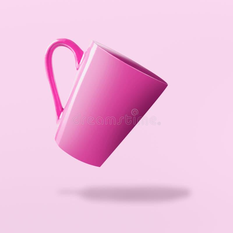 Tazza vuota rosa volante a fondo rosa immagine stock libera da diritti