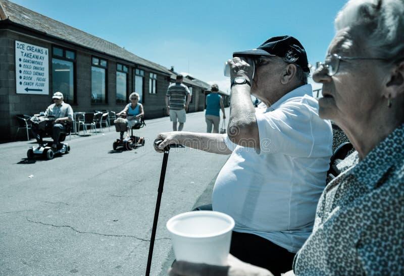 Tazze beventi delle coppie anziane di tè sulla spiaggia inglese fotografia stock