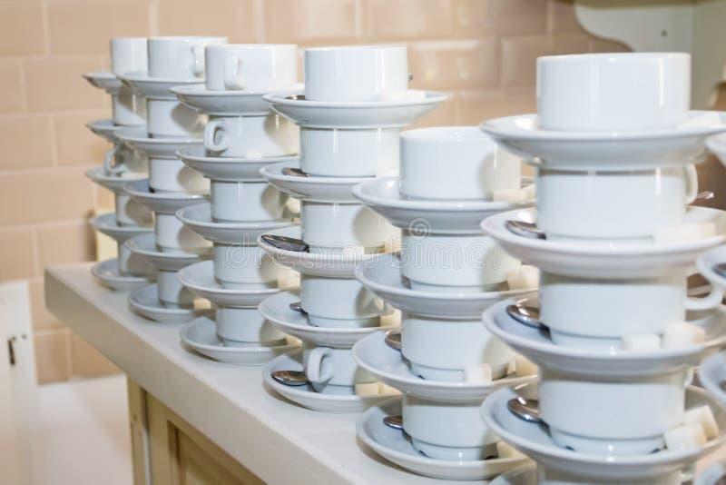 Tazze bianche vuote, piattini con un pezzo di zucchero e cucchiaini fotografie stock libere da diritti