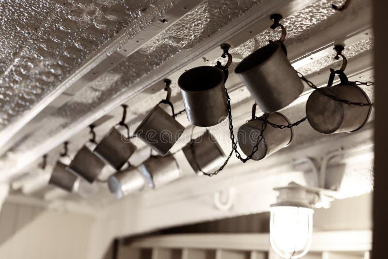 Tazze del metallo dell'acqua sul soffitto immagine stock libera da diritti