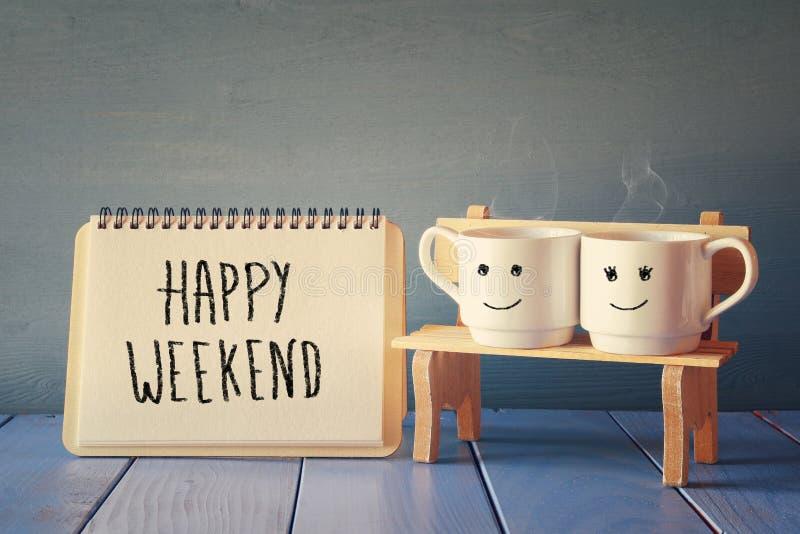 tazze di caffè accanto al taccuino con il fine settimana felice di frase immagini stock libere da diritti