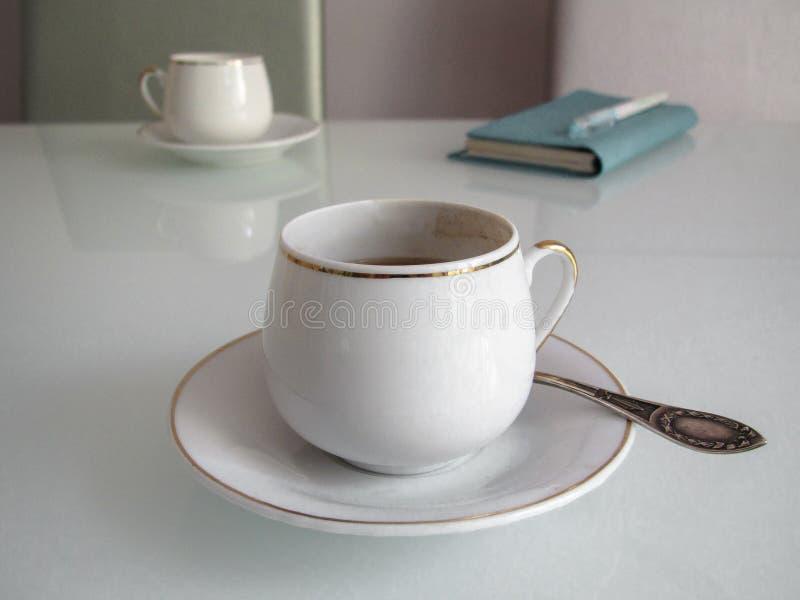 Tazze di caffè con caffè espresso ed il taccuino fotografie stock