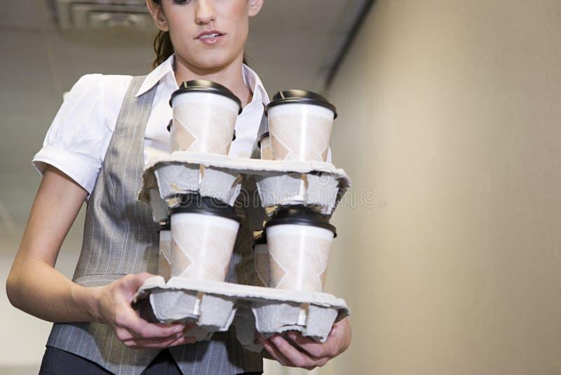 Tazze di caffè di trasporto della donna fotografia stock libera da diritti