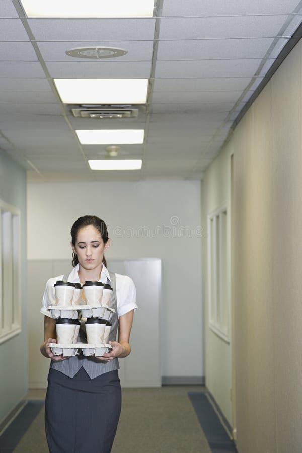 Tazze di caffè di trasporto della donna fotografie stock