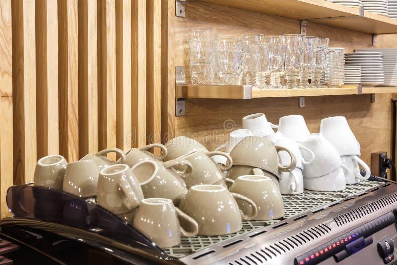 Tazze di caffè sulla macchina del caffè nella barra popolare dell'elite immagine stock