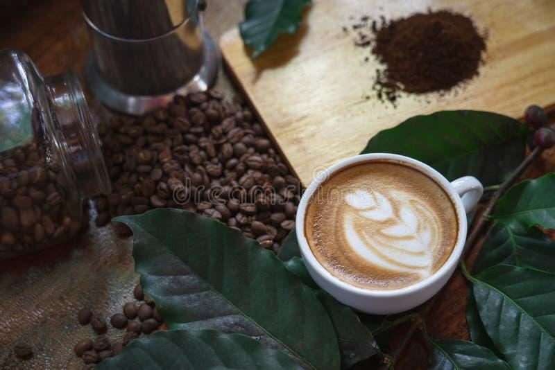 Tazze di caff? macchiato e chicchi di caff? versati su una tavola di legno, meravigliosamente sistemato, decorata con le foglie d immagini stock