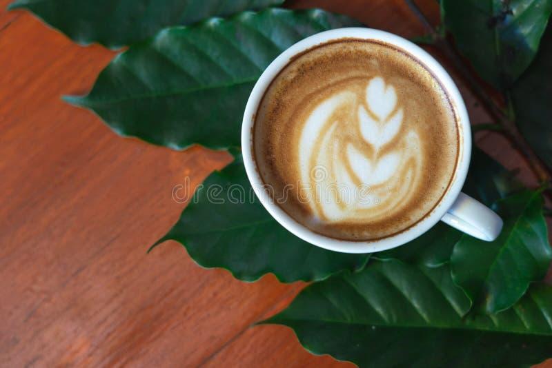 Tazze di caff? macchiato e chicchi di caff? versati su una tavola di legno, meravigliosamente sistemato, decorata con le foglie d fotografie stock