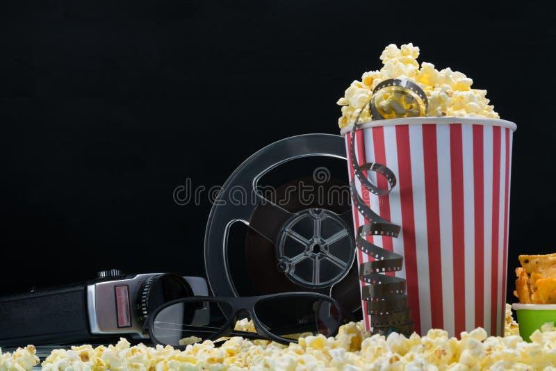 Tazze di carta e film da una vecchia videocamera su popcorn fotografie stock libere da diritti