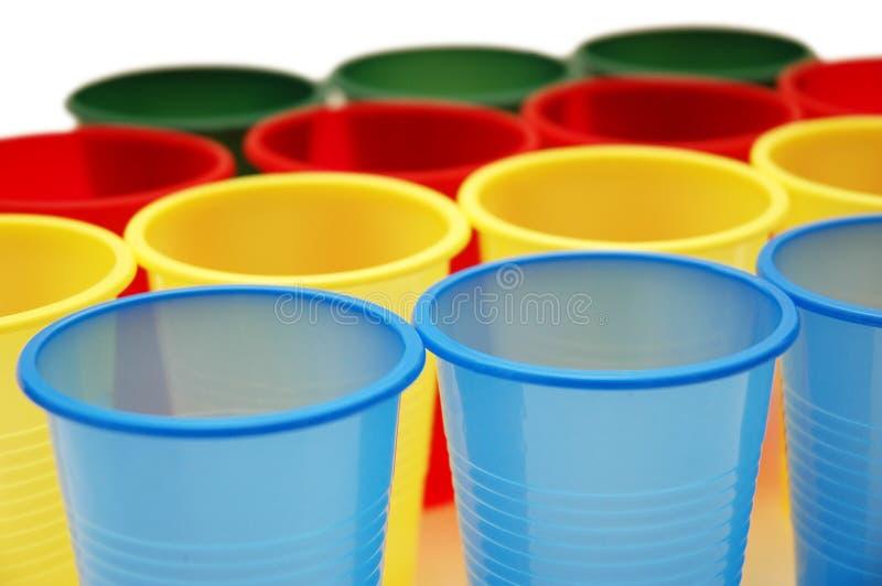 Tazze di plastica di vari colori isolati su bianco fotografie stock