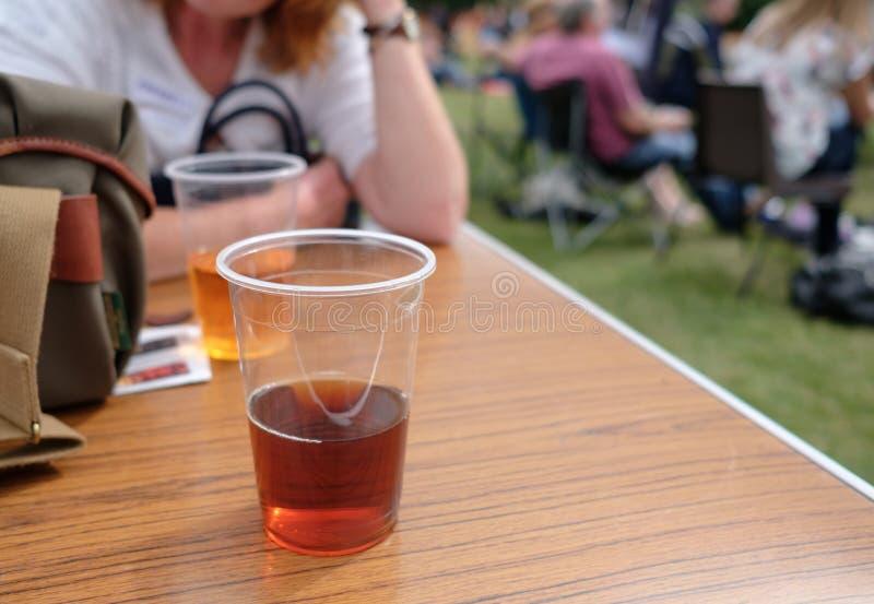 Tazze di plastica isolate della birra e del sidro della pinta su una tavola, veduta ad un festival di musica fotografie stock libere da diritti