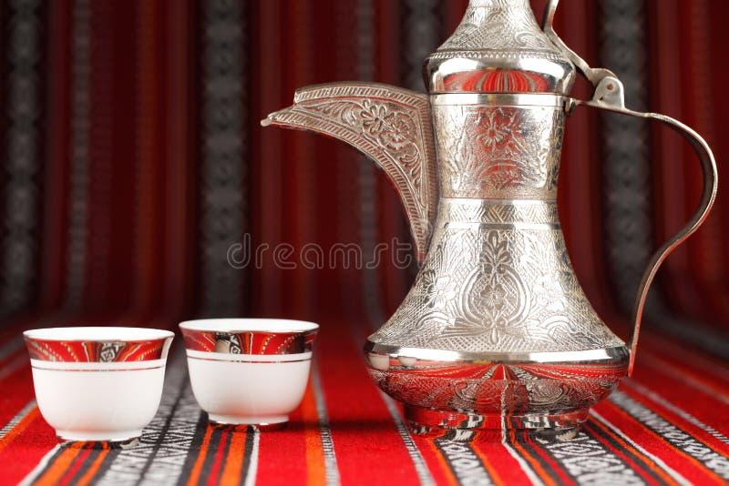 Tazze di tè arabe decorate e una teiera del dallah fotografia stock libera da diritti
