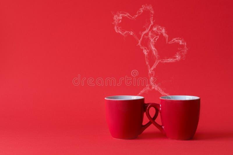 Tazze di tè o di caffè con vapore in una forma di due cuori su fondo rosso Celebrazione di San Valentino o concetto di amore Copi fotografia stock libera da diritti