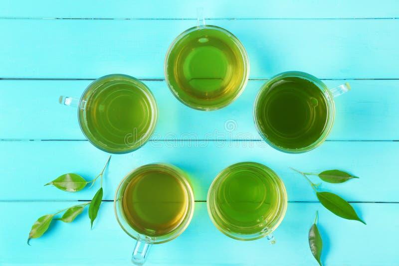 Tazze di tè verde su fondo di legno, fotografia stock