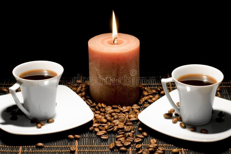 Tazze e la candela sui precedenti neri. immagine stock