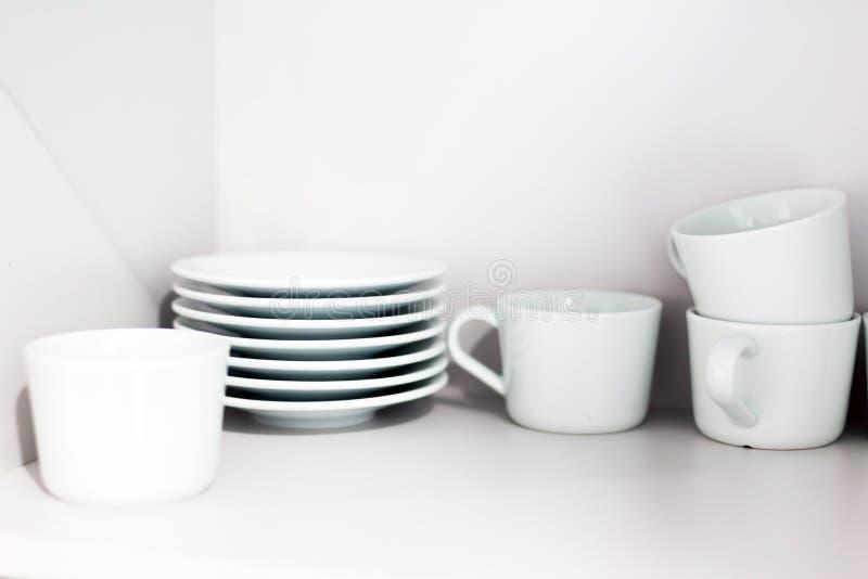 Tazze e piattini di caffè ceramici bianchi sugli scaffali Scaffali con gli utensili della cucina fotografie stock