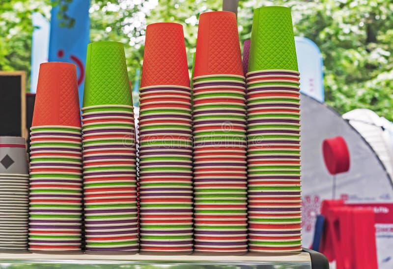 Tazze eliminabili luminose sul contatore di un caffè all'aperto Tazze di carta per varie bevande immagine stock libera da diritti