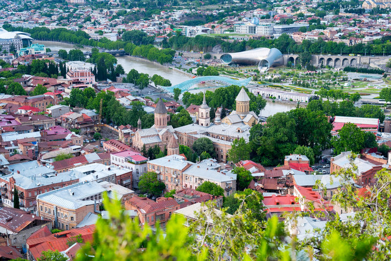 Tbilisi, aerial cityscape. Tbilisi Old Town in the mid of May. Roofs of houses, churches, trees and Kura River with the Bridge of Peace with some defocused green royalty free stock photography