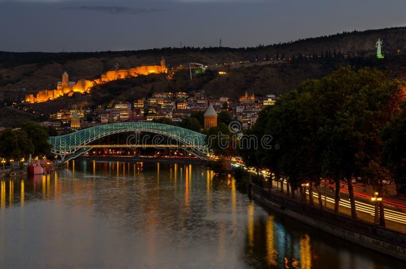 Tbilisi del centro ponte di pace fatto da vetro, dal fiume Mtkvari e dalla fortezza antica famosa di narikala sulla collina Scena fotografie stock