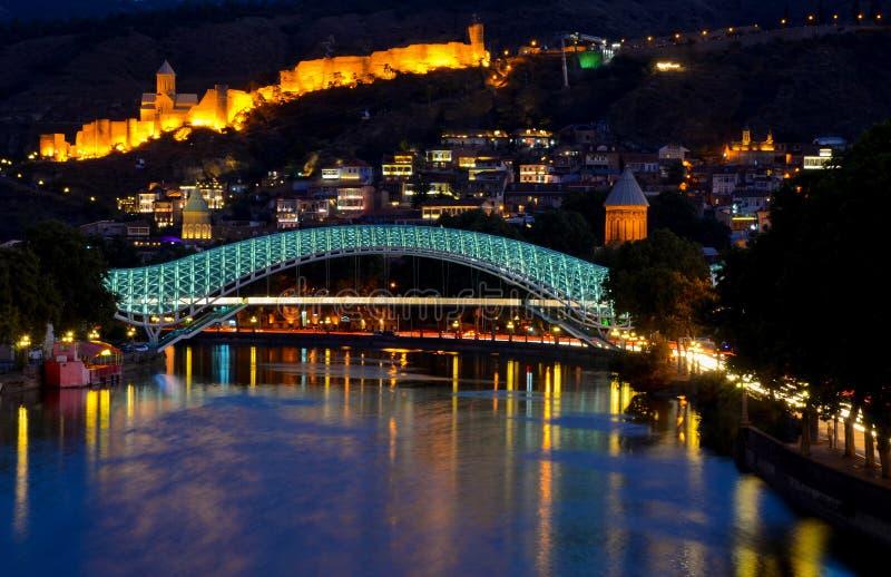 Tbilisi del centro ponte di pace fatto da vetro, dal fiume Mtkvari e dalla fortezza antica famosa di narikala sulla collina Scena immagini stock
