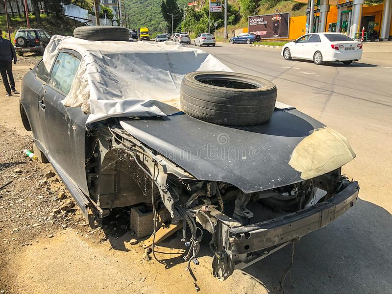 TBILISI, GEORGIË - - 17 MEI, 2018: Een oude gebroken die auto met geteerd zeildoek met een band op de bonnet wordt behandeld bij  royalty-vrije stock afbeeldingen