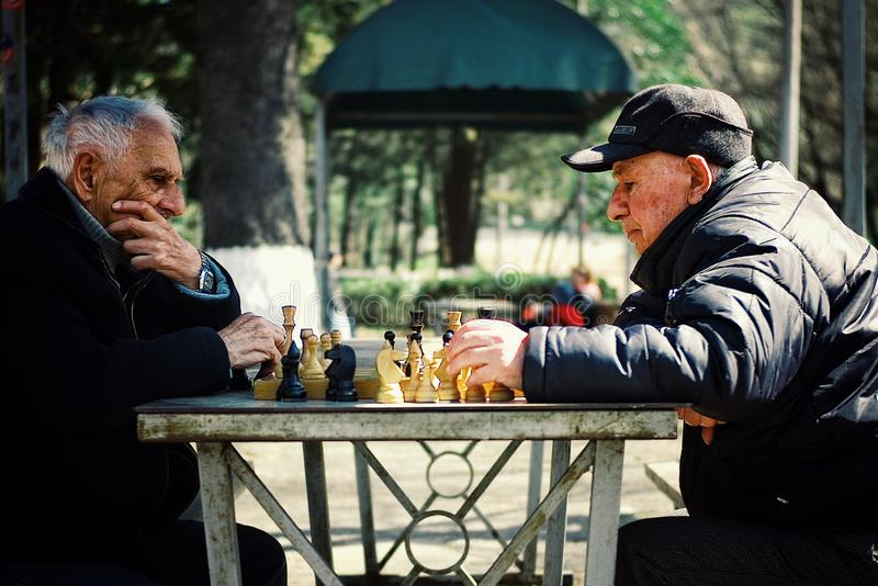 two senior elderly man playing chess in a public park stock photos