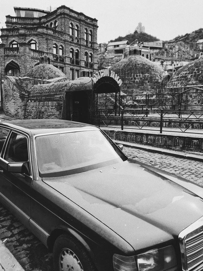 Old car on the street of tbilisi. Tbilisi, Georgia - december, 2018. Backyard in old town. Traditional georgian patio and old car royalty free stock image