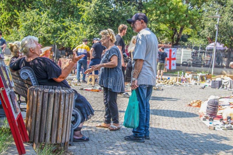 Tbilisi Georgia - Georgiska kvinnor som pratar i skuggan på en ljusstark solnydag på Dry Bridge loppa Market i Tbilisi arkivfoton