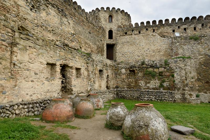 Tbilisi, Georgia-May,6 2019: Courtyard of Svetitskhoveli Cathedral. Part of fortress wall with watchtower and old kvevri vessels stock photography